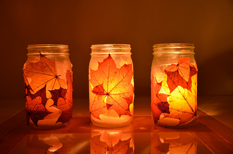 Lamparas con velas en bote de cristal con hojas de los arboles